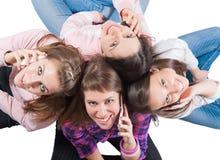 Vier jonge mensen die op wit zitten stock afbeeldingen