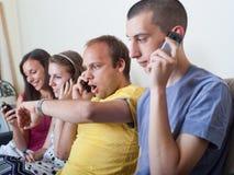 Vier jonge mensen op hun telefoons Stock Afbeeldingen