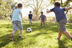 Vier jonge schooljongens die voetbal samen in het park spelen royalty-vrije stock afbeelding