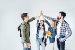 Vier jonge studenten in vrijetijdskleding boeken houden en highfive geven die royalty-vrije stock afbeeldingen
