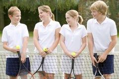 Vier jonge vrienden bij tennisbaan het glimlachen stock fotografie