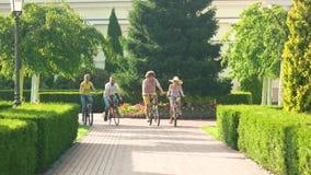 Vier jonge vrienden die op fietsen berijden stock videobeelden
