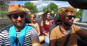 Vier jonge vrienden die pret het berijden in convertibel hebben stock footage