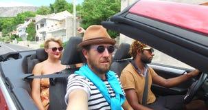 Vier jonge vrienden die van hun wegreis in convertibele auto genieten stock videobeelden