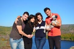 Vier Jonge vrienden en hond die op een meerachtergrond koesteren Royalty-vrije Stock Foto's