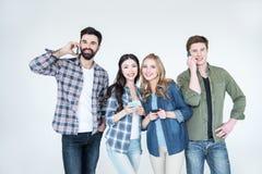Vier jonge vrienden in vrijetijdskleding die smartphones gebruiken stock fotografie