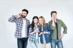 Vier jonge vrienden in vrijetijdskleding die smartphones gebruiken royalty-vrije stock afbeeldingen