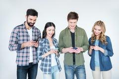 Vier jonge vrienden in vrijetijdskleding die smartphones gebruiken royalty-vrije stock foto