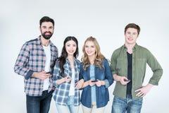 Vier jonge vrienden in vrijetijdskleding die smartphones gebruiken royalty-vrije stock afbeelding