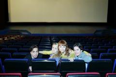 Vier jonge vrienden zitten op zetels in bioskooptheater Stock Foto