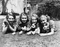 Vier jonge vrouwen die buiten met babykuikens liggen (Alle afgeschilderde personen leven niet langer en geen landgoed bestaat Lev stock foto's