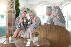 Vier jonge vrouwen die thee drinken bij kuuroordtoevlucht Stock Foto