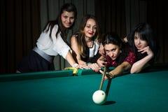 Vier jonge vrouwen hebben pret met het spelen van biljart royalty-vrije stock fotografie