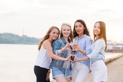 Vier Jonge Vrouwen in Studio die zich in Lijn bevinden en tonen hartgebaar met wapens openlucht royalty-vrije stock foto's