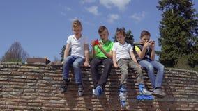 Vier jongens zit bij concrete muur en het ontspannen stock video