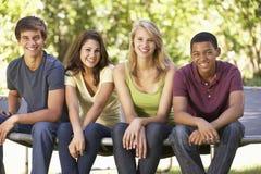 Vier Jugendfreunde, die auf Trampoline im Garten sitzen lizenzfreie stockfotos