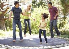 Vier Jugendfreunde, die auf Trampoline im Garten springen stockfotografie