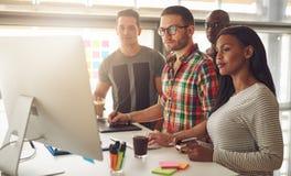Vier junge Arbeitnehmer, die um Computer stehen Stockbilder