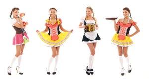 Vier junge bayerische Mädchen, die in den reizvollen Kleidern aufwerfen Lizenzfreie Stockbilder
