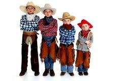 Vier junge Cowboybrüder, die mit den Armen stehen, falteten ernsten exp Lizenzfreie Stockfotografie