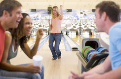 Vier junge Erwachsene, die in einer Bowlingbahn zujubeln Stockbild