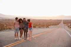 Vier junge erwachsene Freunde, die auf der Wüstenlandstraßenunterhaltung stehen stockfoto