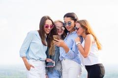 Vier junge Frauen in der Sonnenbrille benutzen den Smartphone, der auf dem Dach des Gebäudes steht Freundschaft und moderne Techn stockfotos