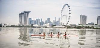 Vier junge Frauen, die auf einem Fluss rudern lizenzfreie stockfotos