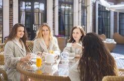 Vier junge Frauen, die Tee am Kurort trinken stockfoto
