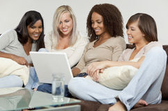 Vier junge Frauen-Freunde, die Spaß mit Laptop haben Stockfotos