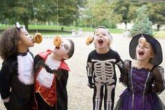 Vier junge Freunde auf Halloween in den Kostümen Lizenzfreie Stockfotos