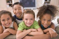 Vier junge Freunde, die heraus zu Hause hängen Lizenzfreie Stockbilder