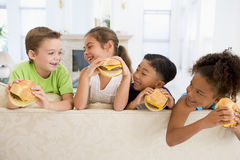 Vier junge Kinder, die Cheeseburger essen Stockfotografie