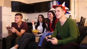 Vier junge Leute, die auf dem Sofa und zwei jungen Männern, die Spiele sitzen spielend, halten Steuerknüppel lizenzfreies stockbild