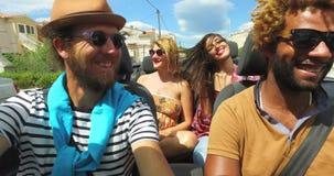 Vier junge Leute, die ihre Autoreise im konvertierbaren Auto genießen stock video
