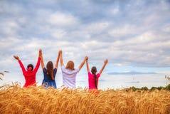 Vier junge Leute, die mit den angehobenen Händen bleiben Lizenzfreie Stockfotografie