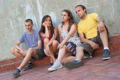 Vier junge Leute, die sich draußen entspannen Stockbilder