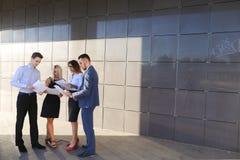 Vier junge Leute, zwei Männer und zwei Frauen, Studenten, stehen in Verbindung, Stockfotos