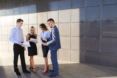 Vier junge Leute, zwei Männer und zwei Frauen, Studenten, stehen in Verbindung, Lizenzfreie Stockfotografie