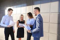 Vier junge Leute, zwei Männer und zwei Frauen, Studenten, stehen in Verbindung, Lizenzfreie Stockbilder