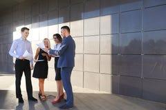 Vier junge Leute, zwei Männer und zwei Frauen, Studenten, stehen in Verbindung, Stockfotografie