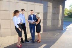 Vier junge Leute, zwei Männer und zwei Frauen, Studenten, stehen in Verbindung, Lizenzfreies Stockfoto
