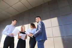 Vier junge Leute, zwei Männer und zwei Frauen, Studenten, stehen in Verbindung, Lizenzfreies Stockbild