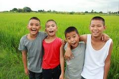 Vier Jungen auf dem Reisgebiet lizenzfreie stockfotos