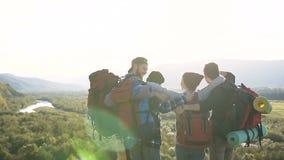 Vier kaukasische Freunde mit Rucksäcken stehen in einem malerischen Ort von Bergen bei Sonnenuntergang still Reisende, die auf di stock video footage