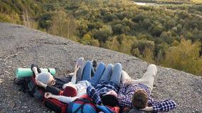 Vier Kaukasische vrienden die op rugzak op de grond in de berg liggen stock videobeelden