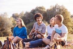 Vier kaukasische weibliche und männliche Freunde lachen froh zusammen, aufwerfen nahe Lagerfeuer, singt Lied auf Akustikgitarre,  lizenzfreie stockfotografie