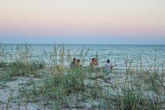 Vier Kerle auf dem Strand mit binokularem am Abend Stockbilder