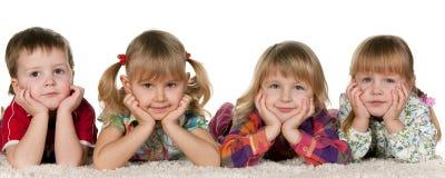Vier Kinder, die auf dem Teppich liegen Stockbild