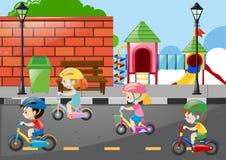 Vier Kinder, die auf die Straße radfahren Stockfotos